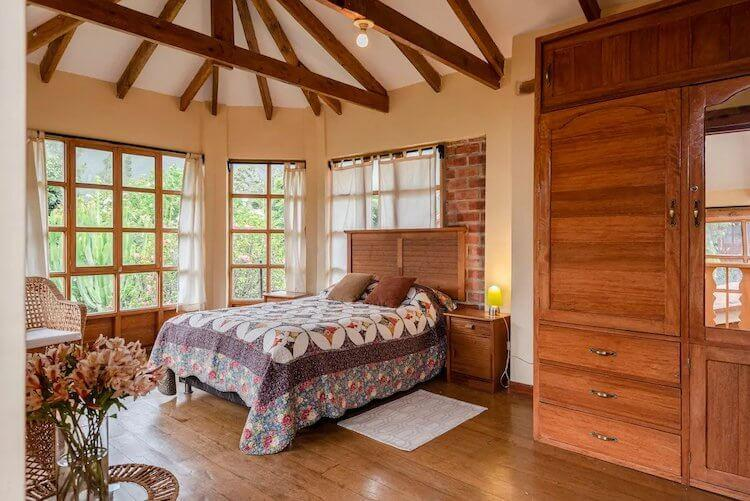 Sacred Valley, Peru Airbnb - Bedroom with big windows, wood beams, and wooden wardrobe
