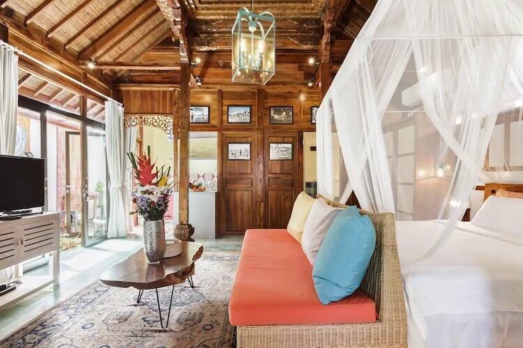 Teak walls and ceiling in a large room with a white bed with bug net in a Bali Airbnb