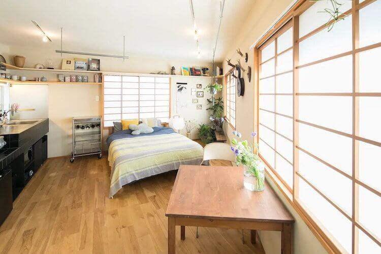 Tokyo Airbnb featuring bright panels on the walls with light, a kitchenette, a green and blue bed, and a table with flowers
