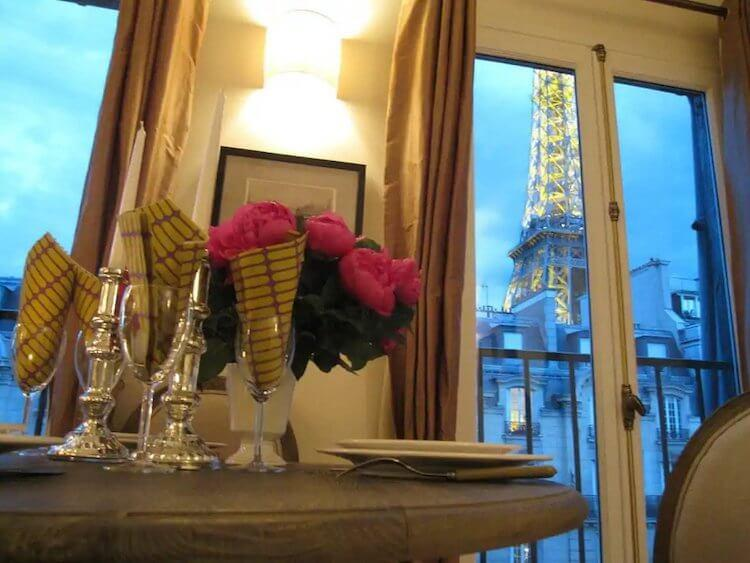 View of the Eiffel Tower Lit at Night from a Paris Honeymoon Airbnb with roses on the table