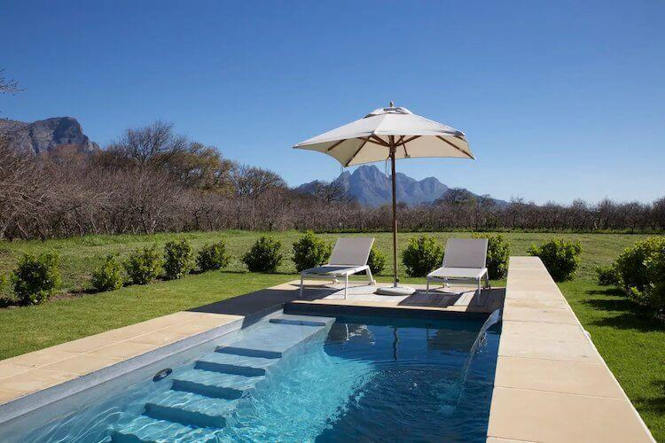 Winelands in South Africa with pool and umbrella in the foreground and mountains in the background