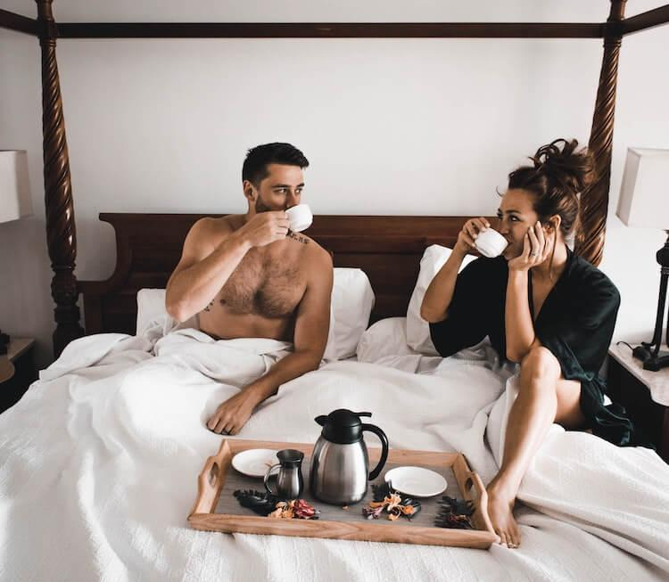 Couple drinking coffee and relaxing in a white bed together