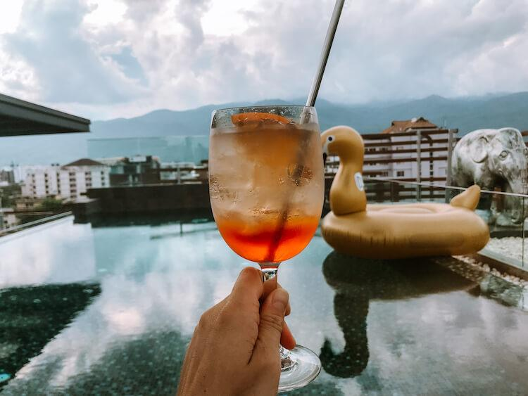 Rooftop pool hotel with a swan float in the background and aperol spritz in the foreground