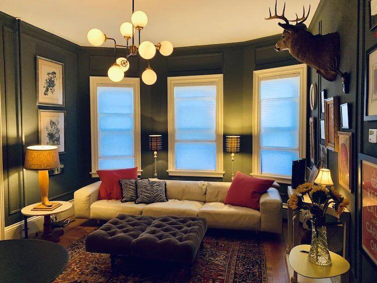 Burlington Chic VRBO Rental with dark green walls, a white couch, stag head, and round bulb chandelier