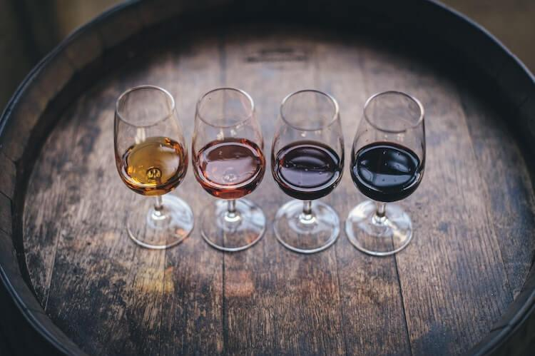4 wine glasses filled with varying types of wine sitting on a barrel