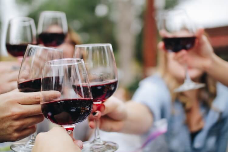 6 people holding up red wine in glasses