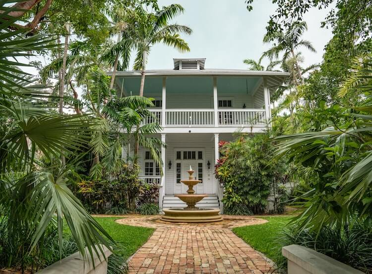 Charming house surrounded by palm trees and has fountain in the front in Key West