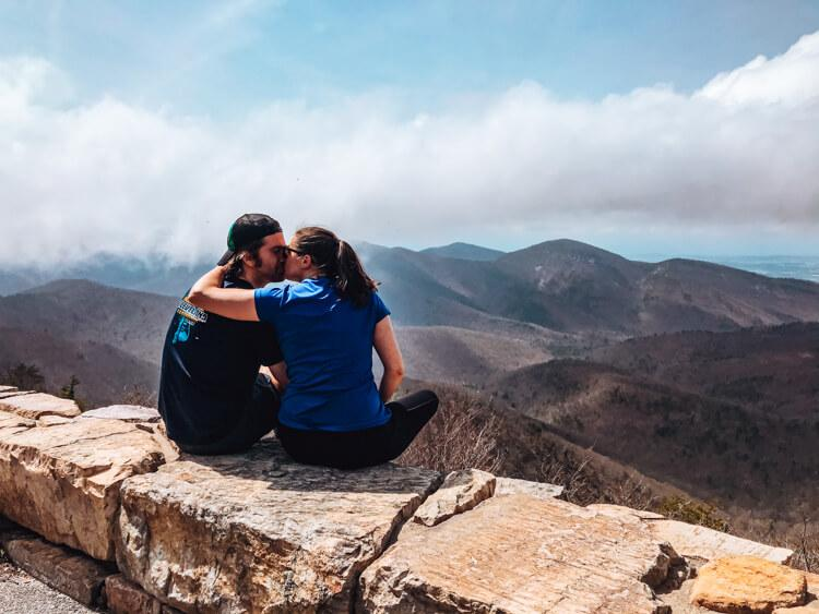 Kat and Chris sitting on a rock wall at an overlook on Skyline Drive and kissing with the mountains in the background