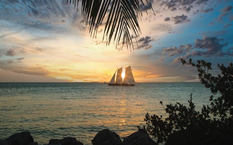 Key West, Florida at sunset with a sailboat in front of the sun and sun peaking through - US Honeymoon Destinations