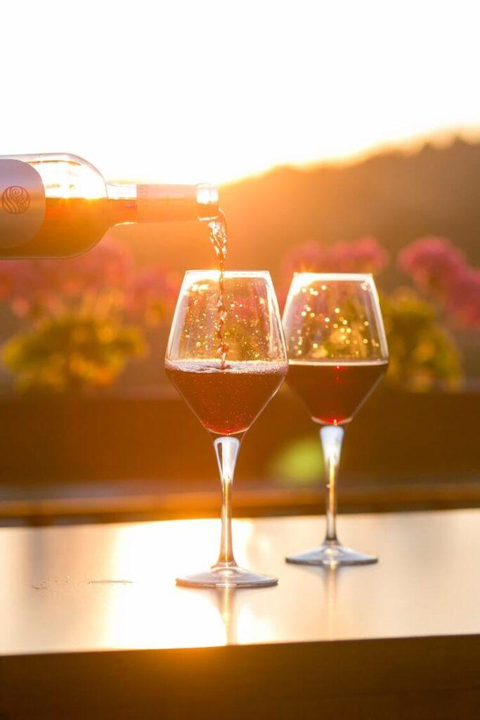 Red wine being poured into a glass as it sits beside another glass with the sunset over a vineyard in the background