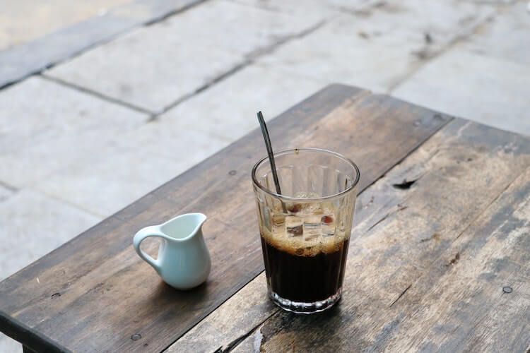 Vietnamese iced coffee sitting on a table next to a milk pourer
