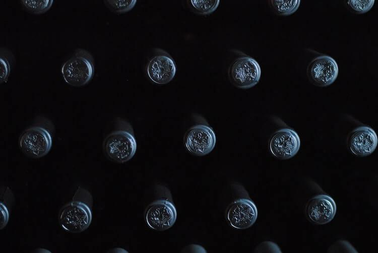 Wine bottles stacked on each other with their black wine sleeves with grapes imprinted on them showing