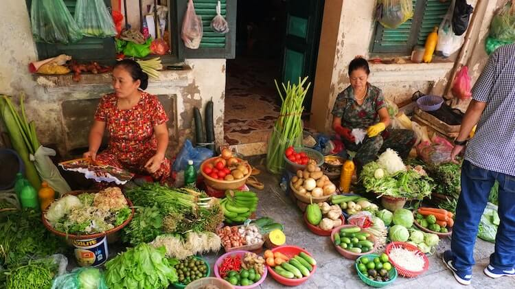 Women sitting down around fruits and vegetables at a market in Hanoi