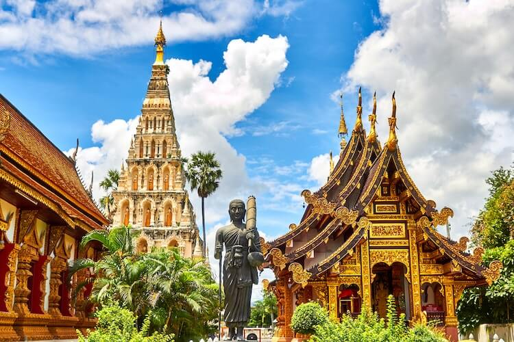 Temples and a Buddha statue on a sunny day in Thailand