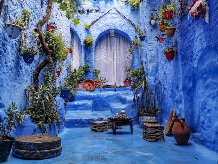 Chefchaouen in Morocco blue city with plants framing a door and seating area