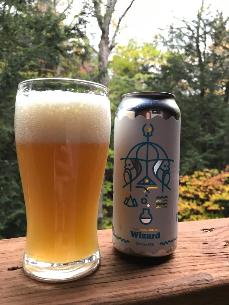 It's Complicated Being a Wizard beer can next to a full beer glass with the woods in the background | Vermont Beer | Best Vermont Breweries