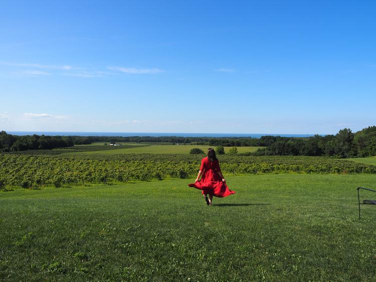 Kat walking toward the vineyard that overlooks Lake Erie in the distance