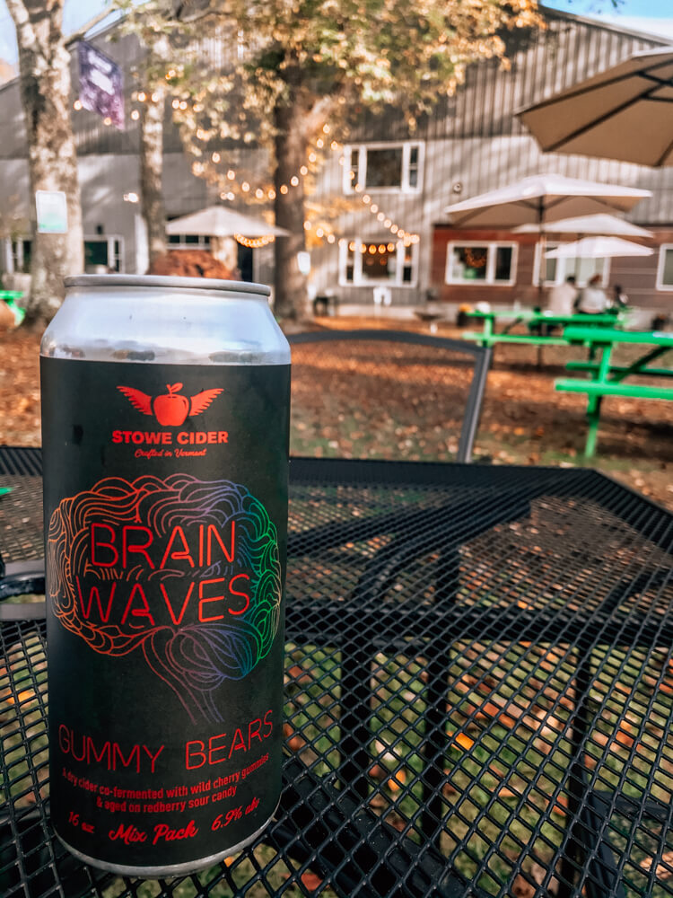 Stowe Cider Brain Waves Can in the back of the cidery with lights in the background. can is sitting on a black patio table - Things to do in Stowe VT - Weekend in Stowe