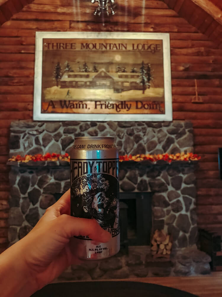 Three Mountain Lodge Sing with Heady Topper Can being held by a hand in the foreground - Weekend in Stowe