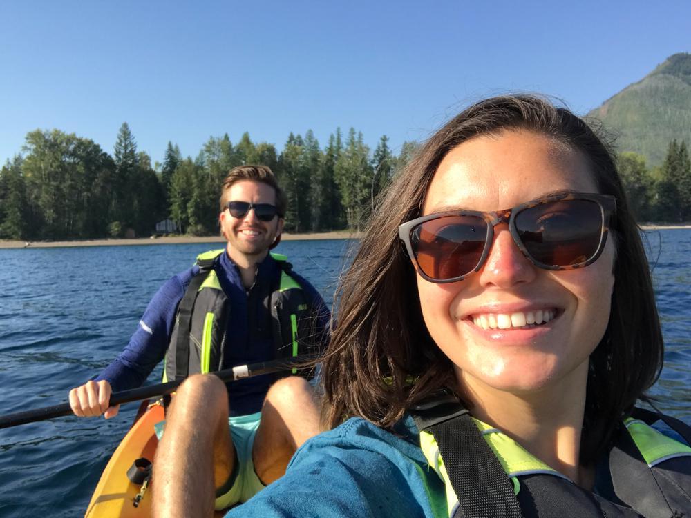 Kat and Chris smiling at the camera and wearing sunglasses while kayaking on Lake McDonald