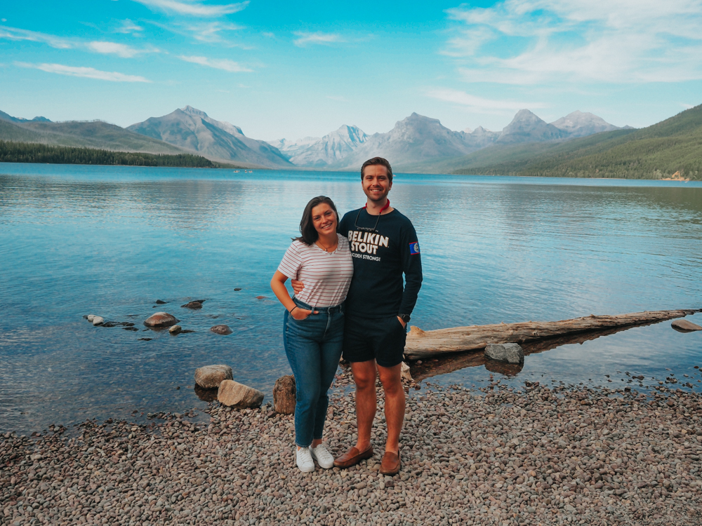 Kat and Chris with an arm around each other and smiling at the camera with Lake McDonald in the background with mountains further back