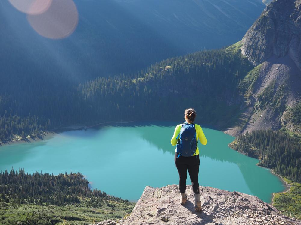 Kat wearing a blue backpack and looking at Grinnell Lake