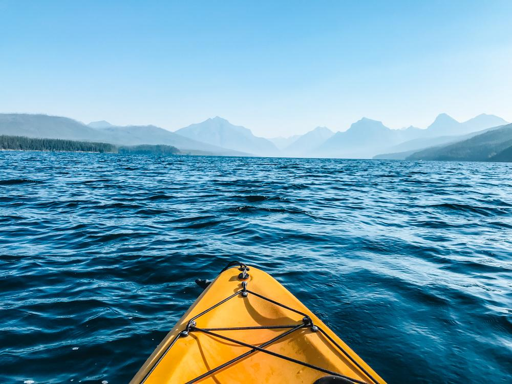 Kayak in the water facing the mountains at Lake McDonald | 7 Days in Glacier National Park