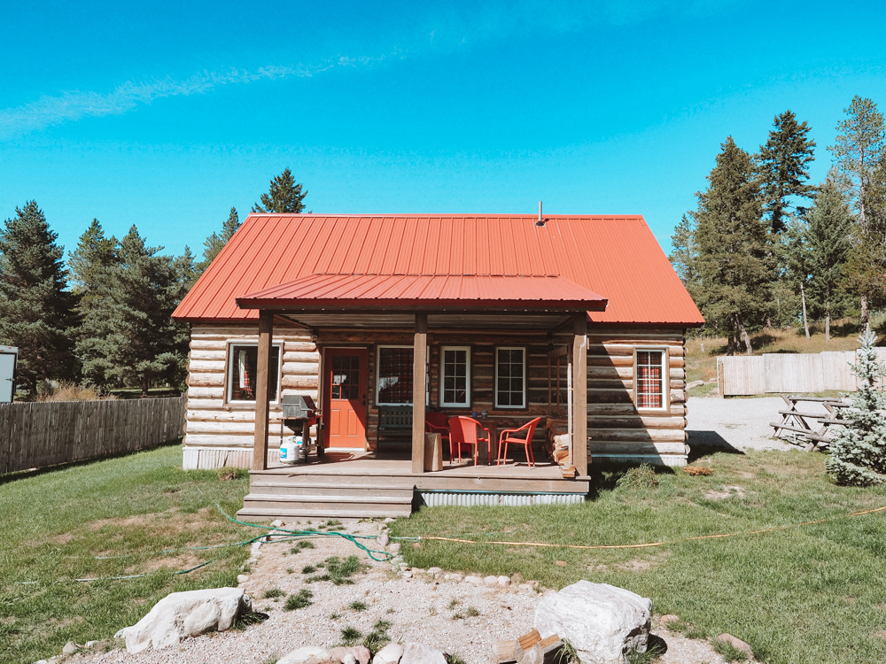 Outside our cabin in West Glacier with log cabin and red roof | Best way to spend 7 days in Glacier National Park