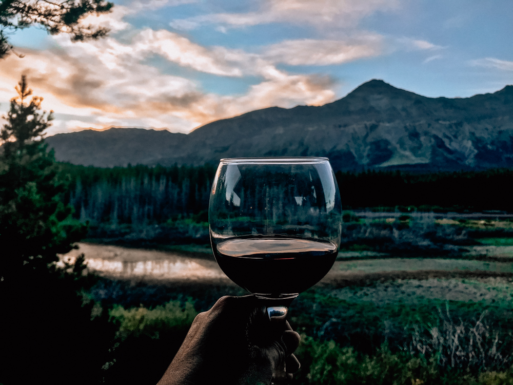 Red wine in a glass being held in a hand with the sunset over the mountains at Summit Mountain Lodge and Steakhouse