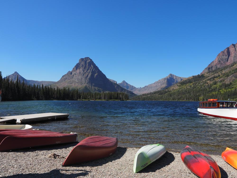 Two Medicine Lake with kayaks resting on the shore turned upside down