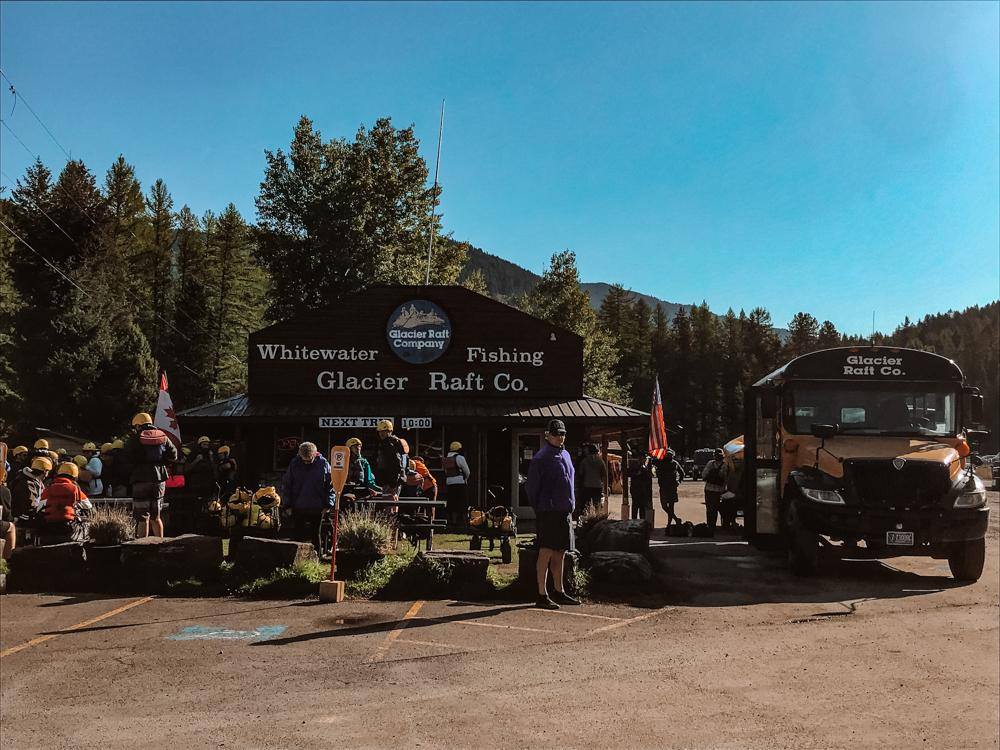 Whitewater Rafting at Glacier Rafting Company | yellow schoolbus on the right facing the camera and people gathered around waiting to start their ride