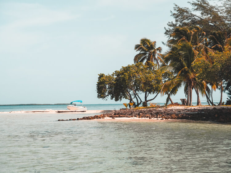Beautiful beach in Belize on an island with boat on sand - Belize itinerary