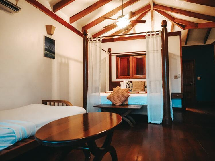Bedroom with wood beams on ceilings, king bed, futon, coffee table, and fan