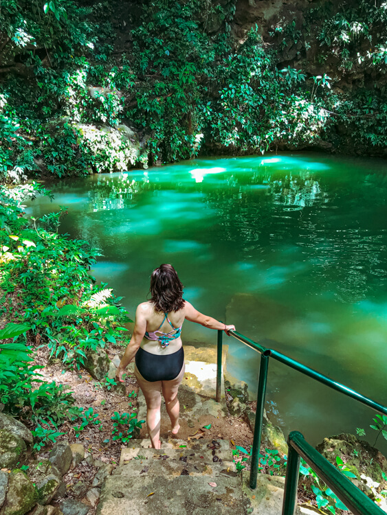 Kat walking into a cenote in Belize - Belize Itinerary